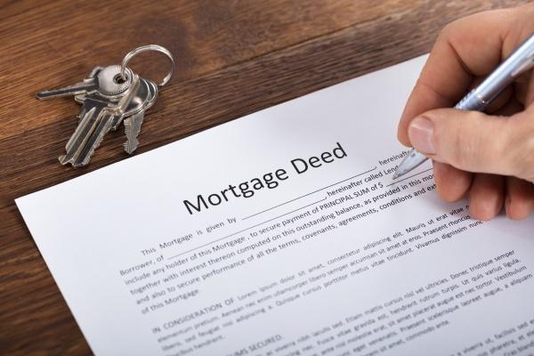 personenhand die ein hypotheken dokument fuellt