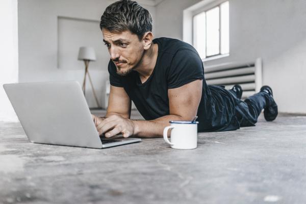 mann liegt mit laptop im leeren