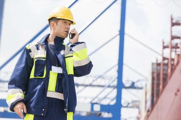 mittelerwachsene maennliche arbeiter mit walkie talkie