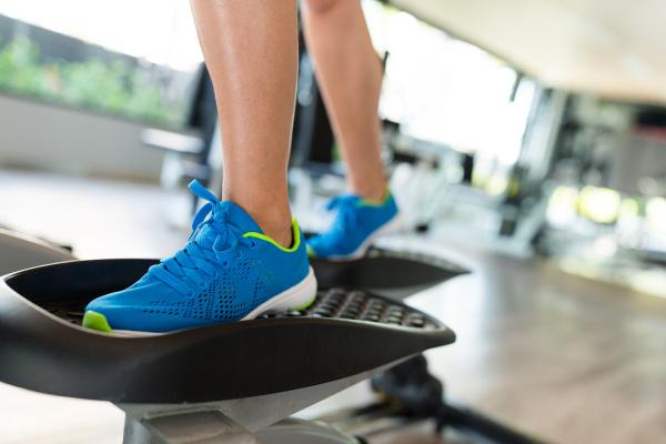 sportfrau trainiert auf ellipsentrainer im fitnessstudio