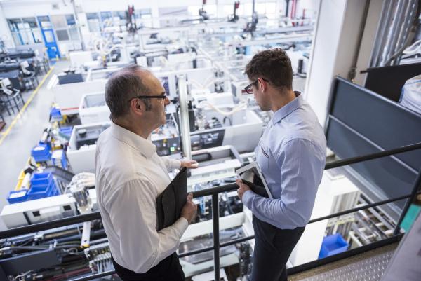 zwei maenner die im fabrikshopboden sprechen