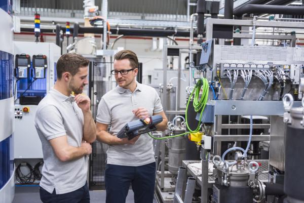 zwei maenner mit kontrolle im fabrikladenboden