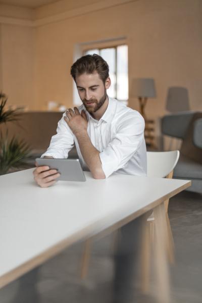junger mann der bei tisch sitzt