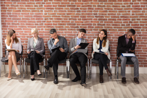 verschiedene geschaeftsleute warten auf job interview