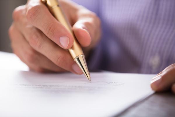 businesspersons hand signing dokument mit stift