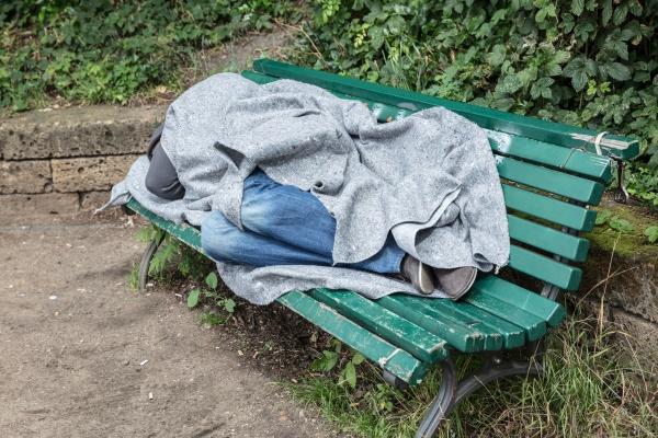 obdachloser mann schlaeft auf bank