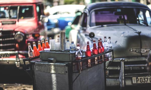 ein getraenkewagen vor geparkten oldtimern der