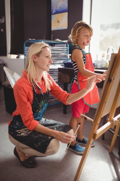 lehrer hilft maedchen in der zeichnungsklasse