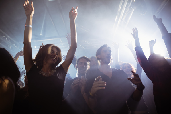 glueckliche menschen tanzen im nachtclub