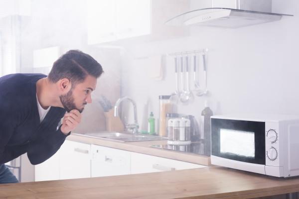 mann der feuerloescher auf mikrowellenherd sprueht