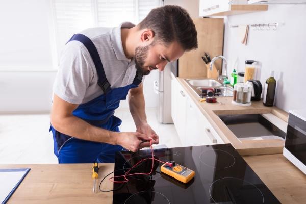 junger reparateur der induktionsherd repariert