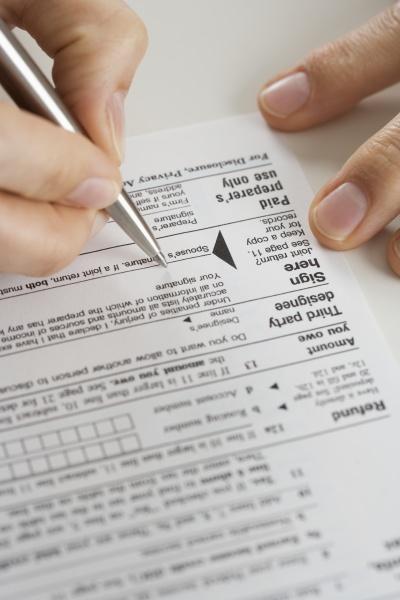 nahaufnahme der haende unterschreiben steuerformular