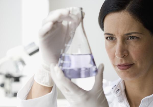 weiblicher wissenschaftler der fluessigkeit im becher