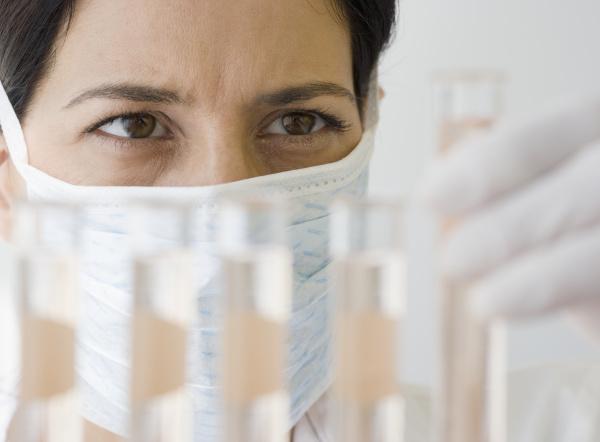 weiblicher wissenschaftler der phiolen fluessigkeit betrachtet