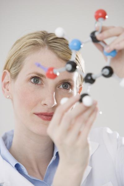 weiblicher wissenschaftler der molekuelmodell betrachtet