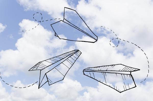 papierflugzeuge auf bewoelktem himmel