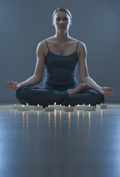 frau meditiert neben kerzen