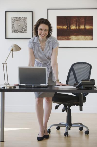 geschaeftsfrau die auf schreibtisch sich lehnt