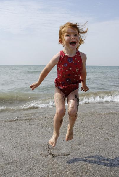 kind hupft am strand in der