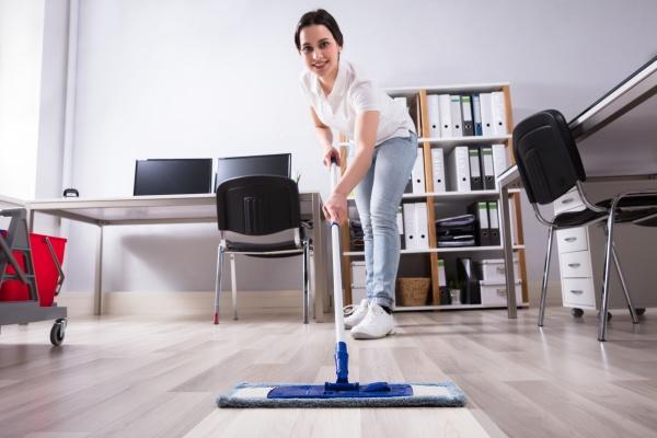 weiblicher janitor reinigungsboden im amt