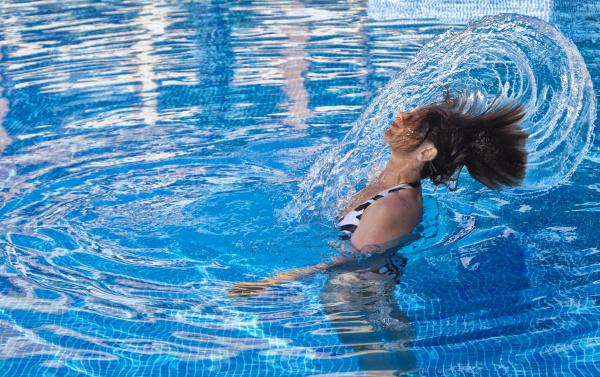 frau im swimmingpool erzeugt eine wasserfontane