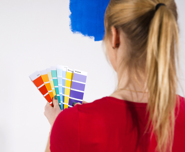 junge frau steht mit farbkarten vor