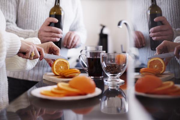 frau schneidet eine orange fuer gluehwein