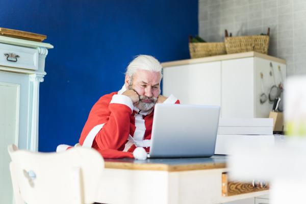 frustrierter weihnachtsmann mit laptop zu hause