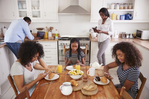 familie die um fruehstueckstisch unter verwendung