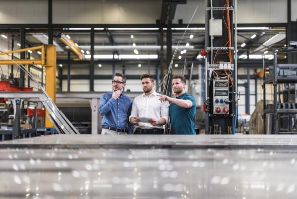 drei maenner die tablette auf fabrikarbeitsboden