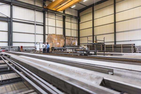 zwei geschaeftsmaenner die auf fabrikarbeitsboden stehen