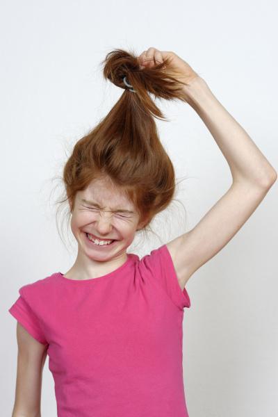 maedchen mit langem haar zupft daran