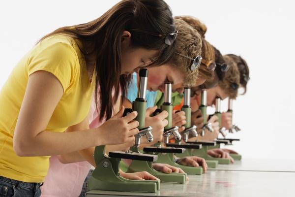 gruppe teenager die mikroskope betrachten
