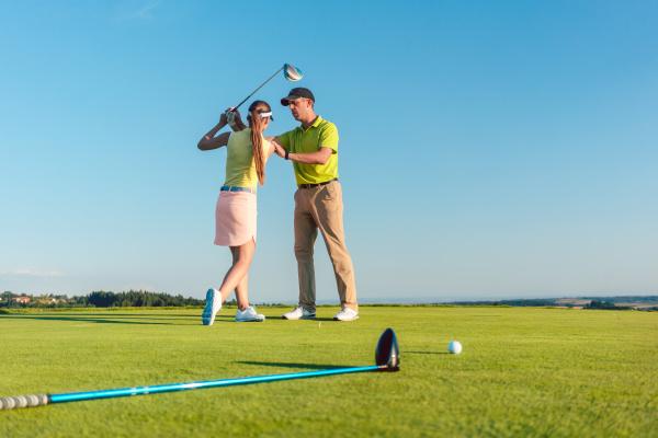 golflehrer der eine junge frau beibringt
