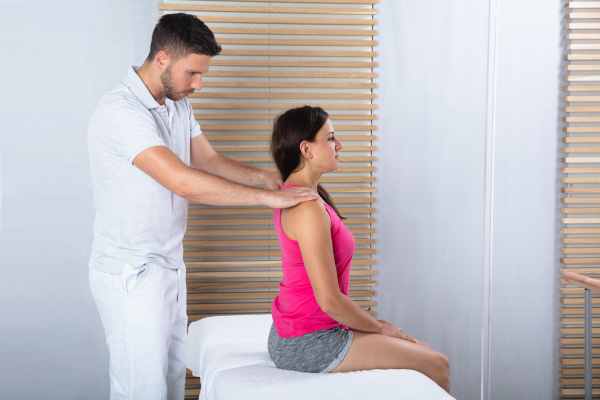 frau erhaelt rueckenmassage vom therapeuten