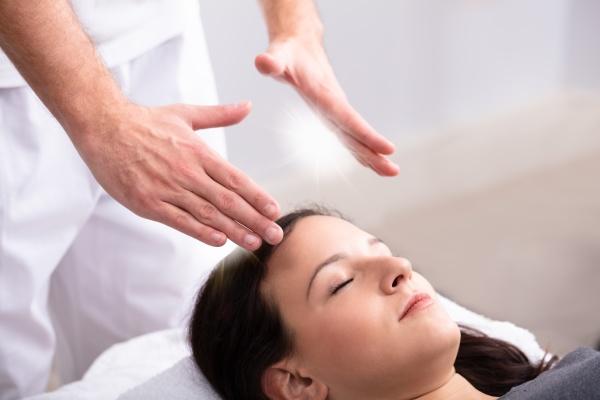 therapeut gibt reiki heilbehandlung fuer frau