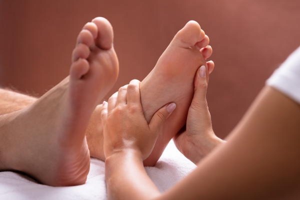 therapeut giving foot massage to man
