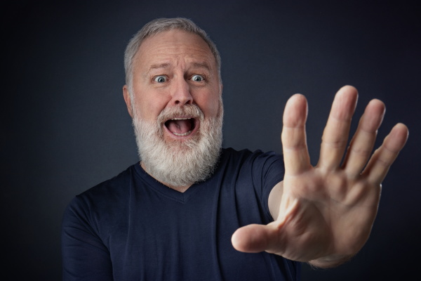 panikter aelterer mann mit gestreckter hand
