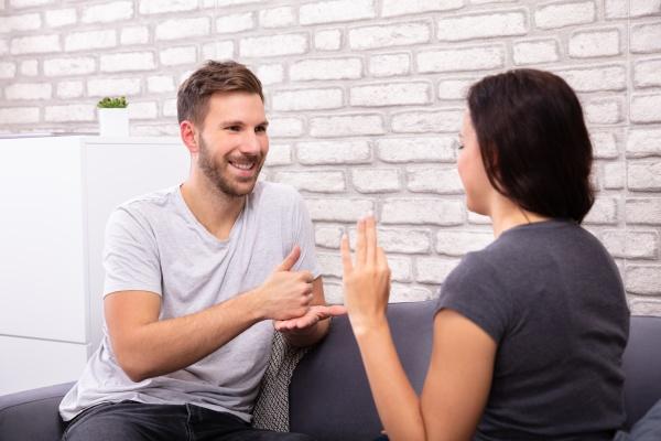 ehepaar kommuniziert mit gebaerdensprache
