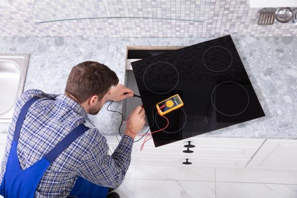 junger reparaturmeister untersucht induktionsherd