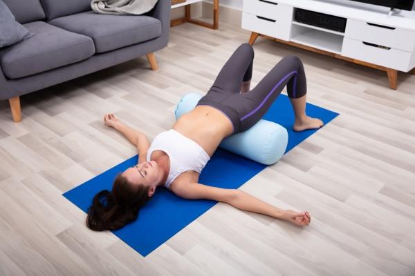 junge frau uebt yoga mit bolster