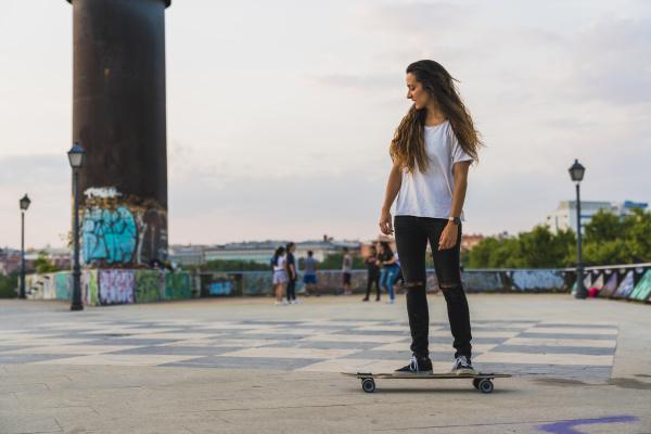 junge frau reitet skateboard in der