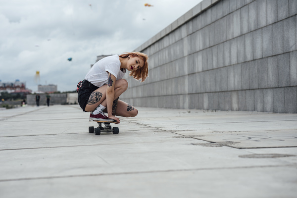 junge frau kauert auf carver skateboard