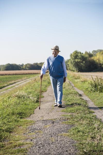 senior mann mit einem gehstock zu
