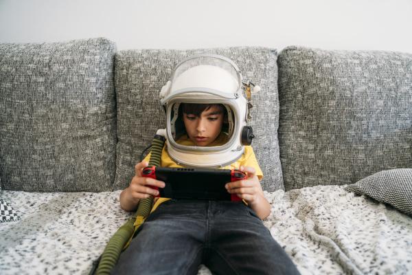 junge spielen videospiel auf einer spielekonsole