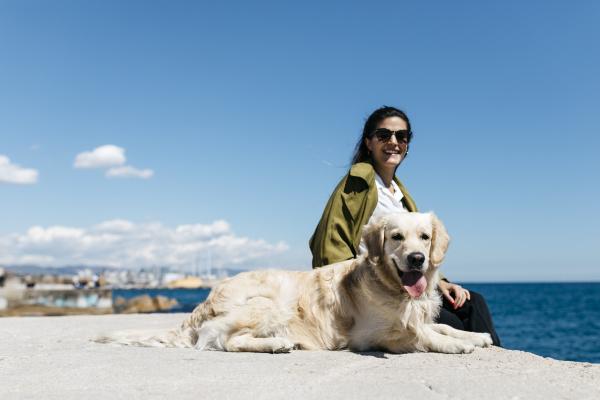 glueckliche frau sitzt neben ihrem labrador