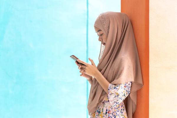 asiatische muslimische studenten benutzen mobiltelefon