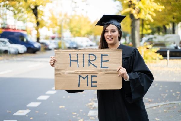 studentin steht mit hire me placard
