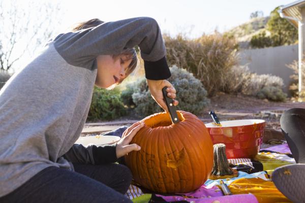 ein sechsjaehriger junge schnitzt zu halloween
