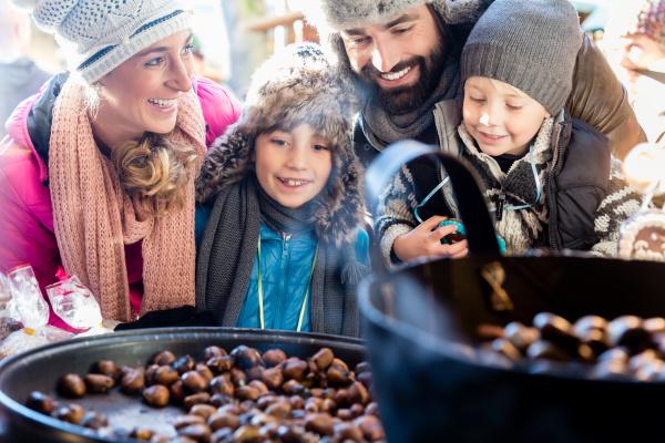 familie auf dem weihnachtsmarkt isst suesse